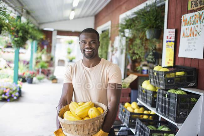 Cheerful man carrying basket of yellow squash vegetables at organic farm market. — Stock Photo