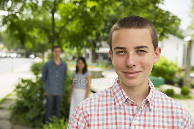 Portrait of boy on street with adults standing in background. — Stock Photo