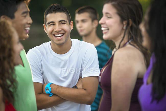 Подросток, стоя с оружием перешли в группе молодых смех друзей на открытом воздухе. — стоковое фото