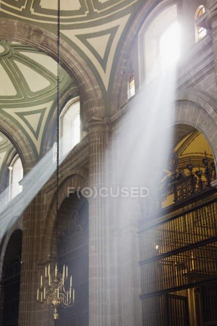 Interior de la Catedral Metropolitana de la Ciudad de México con rayos de sol brillando a través de ventanas - foto de stock