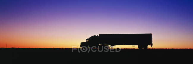 Silhouette of semi-truck against dramatic sky — Stock Photo