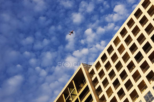 Avión sobrevolando un edificio en Dallas, Texas, EE. UU. - foto de stock