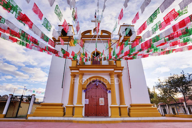 Red, white and green banners on church, Chiapas, Mexico — стокове фото