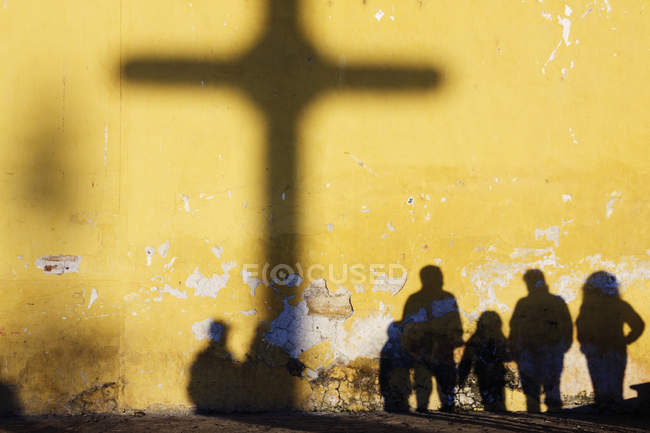 Shadows of cross and people silhouettes against yellow wall — Stock Photo
