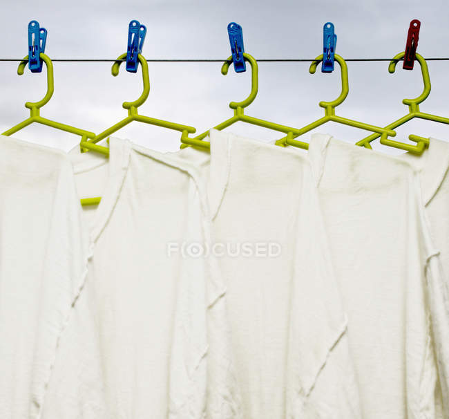 Shirts hanging to dry on green hangers — Stock Photo