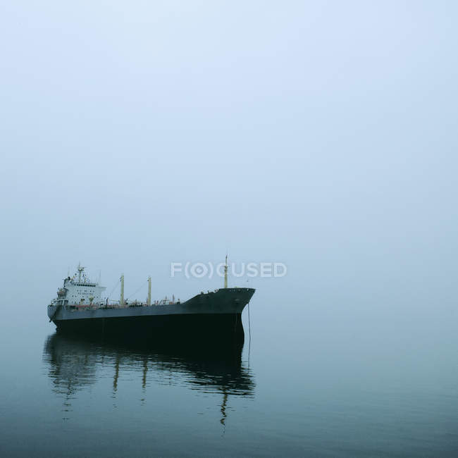 Cargo ship on water in fog with reflection on water surface — Stock Photo