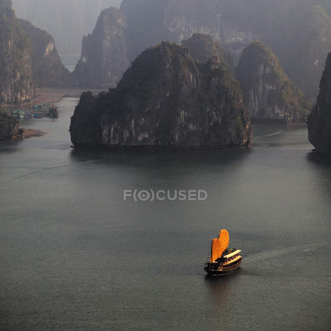 Chinese boat with orange sails on sea water amongst rocks in Halong bay, Vietnam, Asia — стокове фото