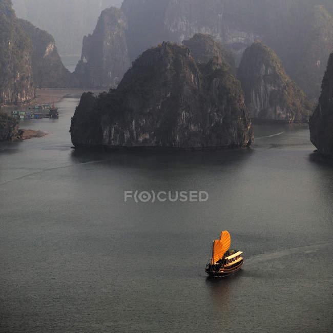 Китайський човен з помаранчевими вітрилами на морській воді серед гірських порід в затоці Халонг, В'єтнам, Азія — стокове фото