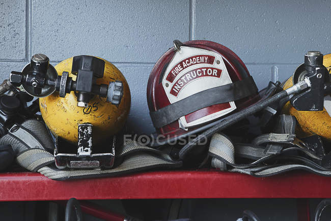 Fireman helmets and gear on shelf, close-up — Stock Photo