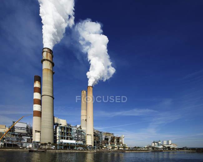 Pilas de humo ondulando humo en planta industrial en Apollo Beach, Florida, EE.UU. - foto de stock