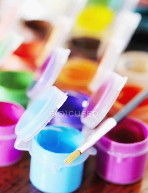 Close-up of multi-colored poster paints and paintbrush — Fotografia de Stock