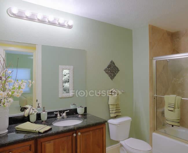 Gut ausgestattetes Badezimmer mit neuen Handtüchern und Spiegel — Stockfoto