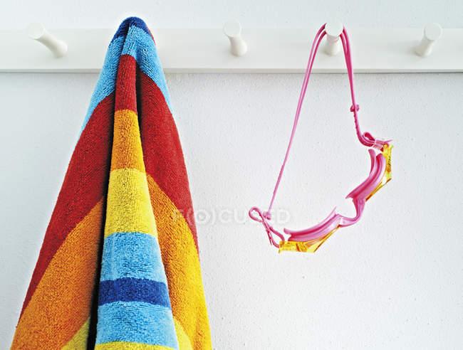 Крупный план пляжного полотенца и очков, висящих в помещении — стоковое фото