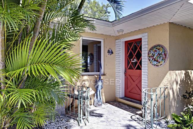 Maison tropicale porte dérobée avec plantes et décoration murale — Photo de stock