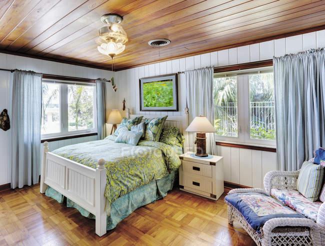 Спальня с деревянным потолком и уютной кроватью — стоковое фото