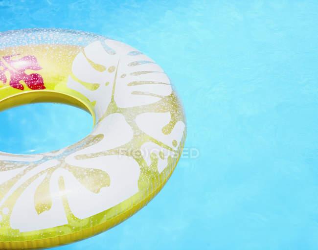 Flutuador inflável do anel da associação na água azul — Fotografia de Stock