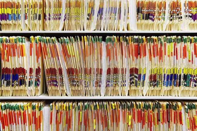 Dossiers médicaux colorés empilés sur des étagères — Photo de stock