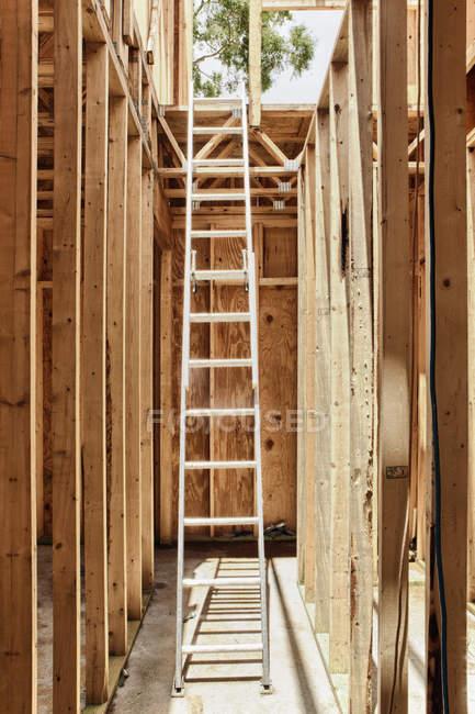 Высокая лестница расширения в недостроенном деревянном здании — стоковое фото
