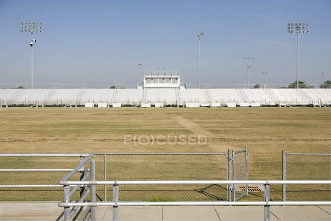 Field, railings and bleachers at high school stadium — Foto stock
