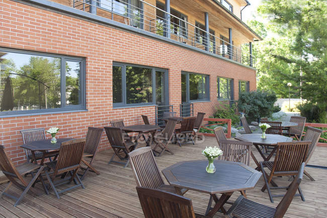 Dining tables and chairs on outdoor hotel deck — Stock Photo