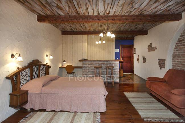 Cama acogedora En habitación de hotel con techo de madera - foto de stock