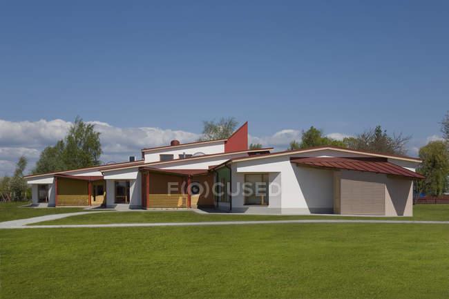 Edifício da escola primária moderna na grama gramado verde — Fotografia de Stock