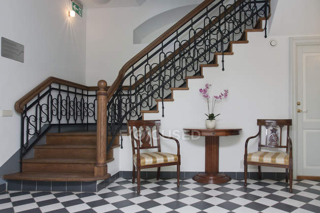 Staircase in elegant hall with chairs and table — Stock Photo
