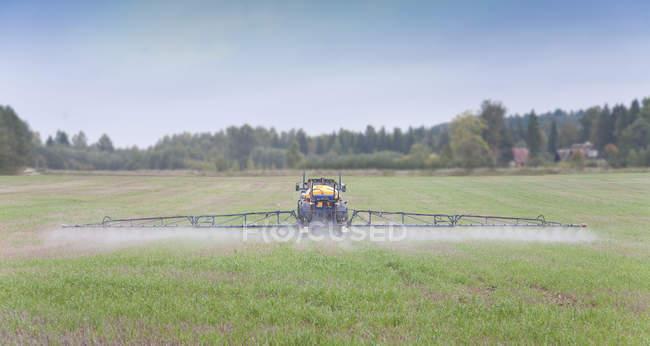 Pulvérisation d'herbicides par tracteur dans un champ rural, Estonie — Photo de stock