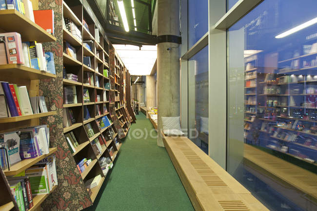 Bookstore reading bench and shelves with books — Stock Photo