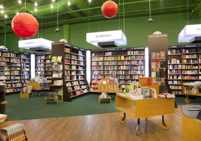 Libros en estantes y mesas en Librería - foto de stock