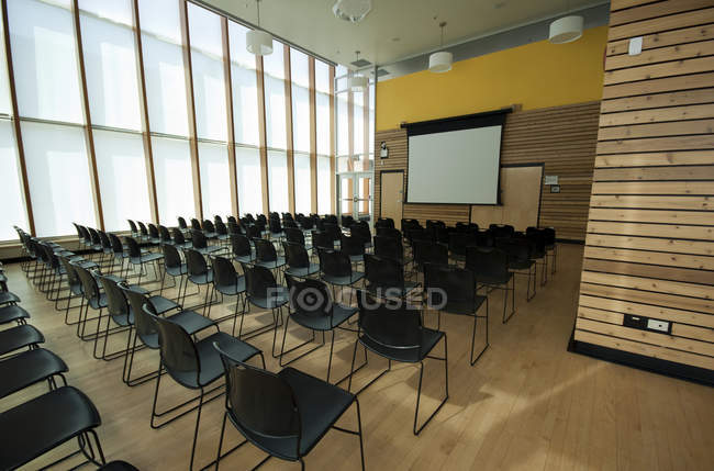 Chairs and projection screen in empty room — Stock Photo