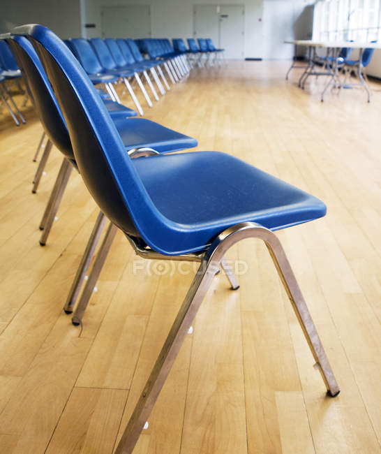 Rows of blue chairs in empty auditorium interior — Stock Photo