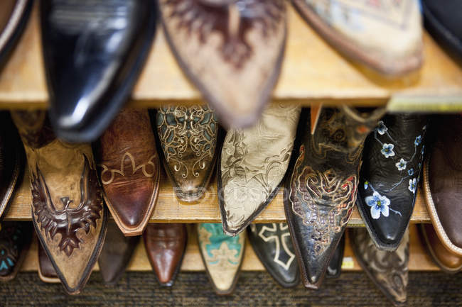 Collection of cowboy boots on shelves — Stock Photo