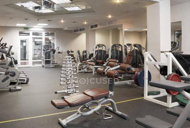 Fitness equipment in empty gym interior — Stock Photo