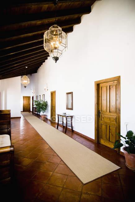 Pasillo en el hotel con lámparas y puertas adornadas - foto de stock
