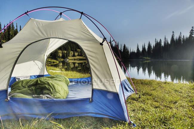 Tente au bord du lac tranquille, parc provincial du lac Bowron, Canada — Photo de stock
