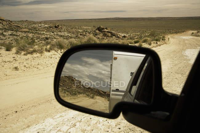 Strada sterrata attraverso il deserto con vista dallo specchio del veicolo — Foto stock