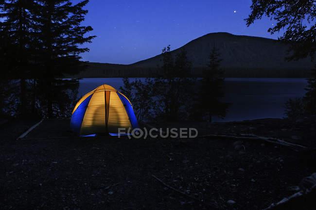 Acampamento com a barraca iluminada na noite, Parque Provincial do Lago Bowron, Canadá — Fotografia de Stock