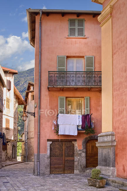 Urban French streetscape with old traditional houses and laundry hanging on balconies, Saint Etienne de Tinee, France — стокове фото