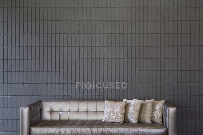 Modern sofa with pillows against brick wall — Foto stock