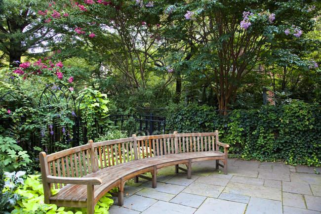 Lunga panchina arrotondata parco in cespugli verdi con fiori — Foto stock