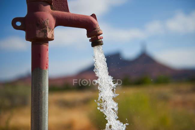 Primer plano del agua procedente del grifo al aire libre - foto de stock