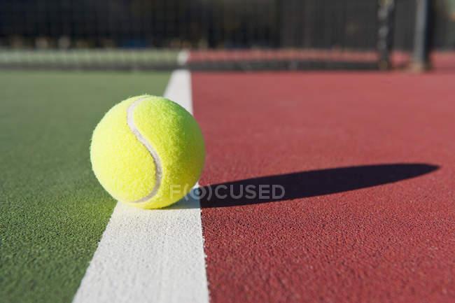 Primer plano de la pelota de tenis en la pista de tenis a la luz del sol - foto de stock