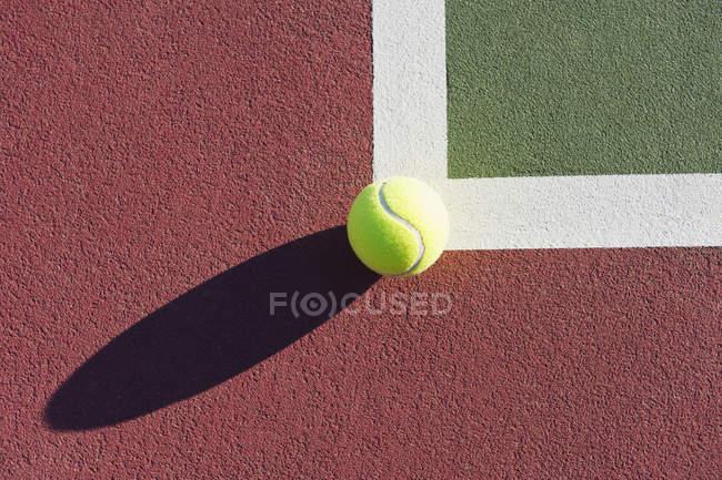 Primer plano de la pelota de tenis en el borde de la cancha de tenis a la luz del sol - foto de stock