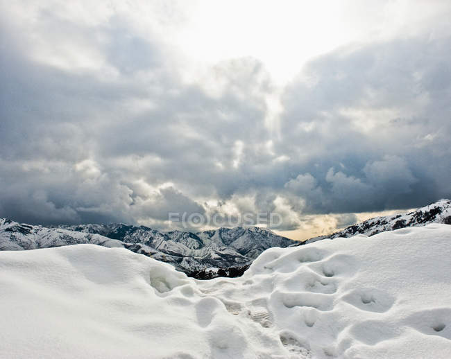Footprints in mountain snow with scenery of hills and cloudscape, Salt Lake City, Utah, USA — Stock Photo