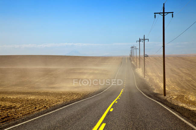 Highway through farmland fields in dust, Oregon, USA — стокове фото