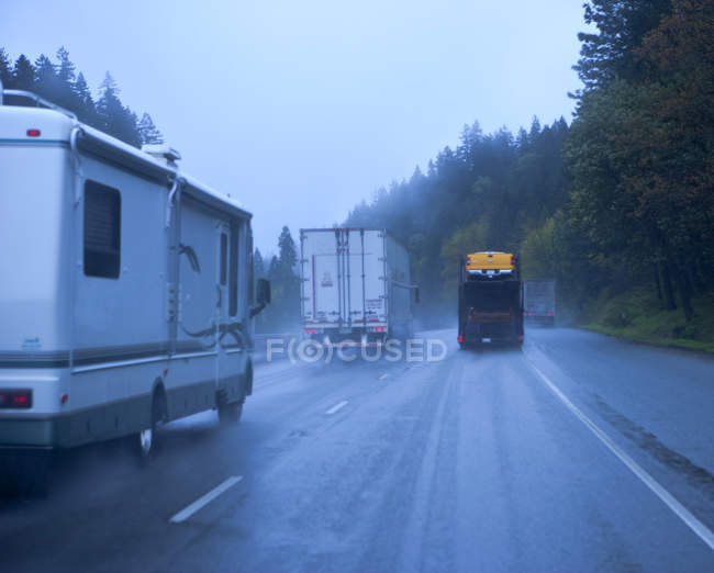 Freeway traffic in rain in countryside woodland road — Stock Photo