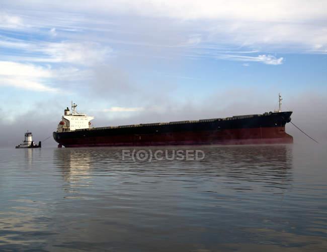 Nave da carico e rimorchiatore in acqua sotto il cielo blu nel fiume Columbia, Oregon, USA — Foto stock