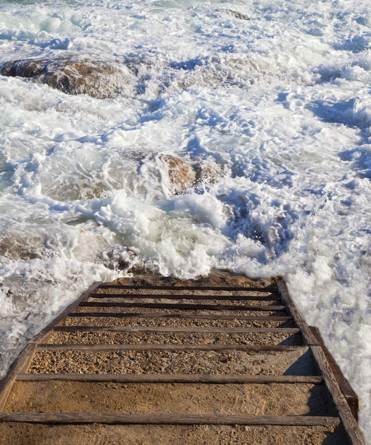 Stairway and rocky steps to ocean water surf — Stock Photo