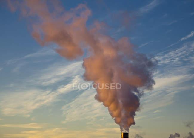 Dampf von Rauchschwaden gefärbt durch Sonnenuntergang gegen wolkenverhangenen Himmel — Stockfoto